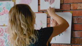 Artwork collection display stick paintings wall. Artwork collection display. Artist sticking paintings on the wall stock footage
