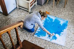 Artwork at home and people doing art painted on the floor in the house - caucasian woman  and blue wall paper - artistic activity
