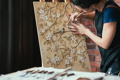 Artwork inspiration woman artist tool canvas easel. Artwork in process. Inspiration. Woman artist with tool creating. Canvas on easel. Flowers and birds pattern stock photography