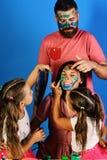 Artyści tworzą guasz grafikę na ladys twarzy Rodzice i dzieci zdjęcie stock