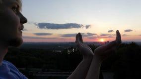 Arty bemannen hält die Sonne in seinen Händen bei Sonnenuntergang in Kyiv in SlomO stock video