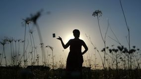 Silhouette of a slender woman throwing a camera in a field at sunset in slo-mo stock video