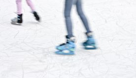 Arty blurry two teenage girl ice skating legs. Fun and winter recreation detail stock photography