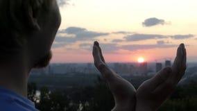 Arty mężczyzna utrzymuje słońce w jego rękach przy zmierzchem w Kyiv w mo zbiory