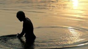 Arty Person Moves His Hand en aguas de río y miradas en la puesta del sol almacen de metraje de vídeo
