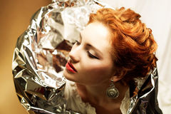 Arty portrait of a fashionable queen-like ginger model. With silver foil cape over white curtain background. Close up. Studio shot stock image