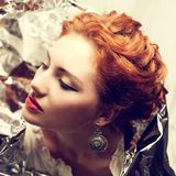 Arty portrait of fashionable queen-like red-haired queen. Arty portrait of a fashionable queen-like red-haired ginger model with silver foil cape posing over stock photography