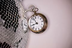 Arty shot of a metal large pocket watch clock next to a silver disco ball. An arty shot of a metal large pocket watch clock next to a silver disco ball on a royalty free stock photos