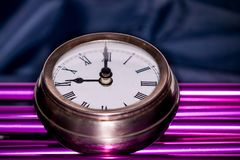 Arty shot of a metal large pocket watch clock on purple pipes. An arty shot of a metal large pocket watch clock on a number of purple pipes royalty free stock photography