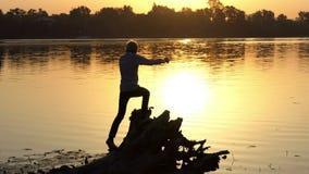 Artymannen hoppar på en sjöbank på en guld- solnedgång stock video