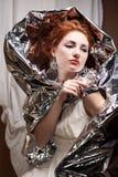 Artystående av en innegrej drottning-som modell med silverfolie royaltyfri fotografi