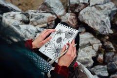 Artysta dziewczyny obrazu obsiadanie na skałach przy falezą, notepad Cudowny spadku widok Obrazy Royalty Free