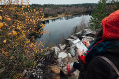Artysta dziewczyny obrazu obsiadanie na skałach przy falezą, notepad Cudowny spadku widok Zdjęcie Stock