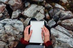 Artysta dziewczyny obrazu obsiadanie na skałach przy falezą, notepad Cudowny spadku widok Zdjęcie Royalty Free
