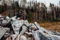 Artysta dziewczyny obrazu obsiadanie na skałach przy falezą, notepad Cudowny spadku widok Fotografia Royalty Free
