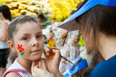 Artysta farb maska na dziewczyny twarzy na children wakacyjni w parku w Volgograd Zdjęcie Stock