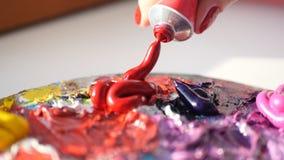 Artysta gniesie od tubki palety purpurowa wazeliniarska farba, HD obrazy stock