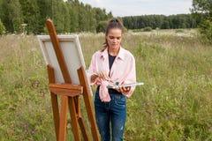 Artysta maluje obrazek w polu zdjęcie royalty free
