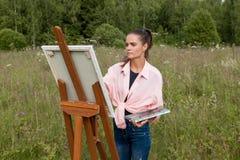 Artysta maluje obrazek w polu zdjęcie stock