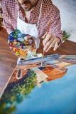 Artysta Maluje Pięknego obrazek na sztaludze w studiu zdjęcie stock