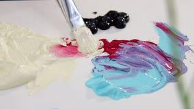 Artysta miesza farby muśnięcie w z kości słoniowej i czerwonego koloru palecie dla mieszać kolory Przygotowywać rysować zbiory wideo
