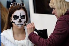Artysta stosuje czaszka makijaż dla gościa Obraz Royalty Free