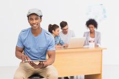 Artysta używa cyfrową pastylkę z kolegami w tle przy biurem Fotografia Stock