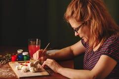 Artysty projektanta kobieta maluje Wielkanocnych przedmioty Używa akwareli muśnięcie Pracy w studiu zdjęcie stock