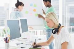 Artysty rysunek coś na graficznej pastylce z kolegami behind przy biurem Zdjęcia Stock