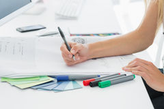 Artysty rysunek coś na papierze z piórem przy biurem Obraz Stock