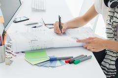 Artysty rysunek coś na papierze z piórem przy biurem Obraz Royalty Free