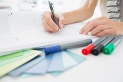 Artysty rysunek coś na papierze z piórem przy biurem Obrazy Royalty Free