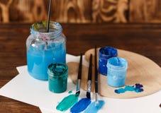 artysty warsztat s Odgórny widok paintbrushes paleta i akrylowe farby z białą kanwą Set muśnięcia i nafciane farby Sztuki pictu Obraz Stock