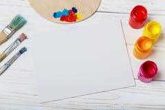 artysty warsztat s Odgórny widok paintbrushes paleta i akrylowe farby z białą kanwą Set muśnięcia i nafciane farby Sztuki pictu Zdjęcie Royalty Free