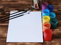 artysty warsztat s Odgórny widok paintbrushes paleta i akrylowe farby z białą kanwą Set muśnięcia i nafciane farby Sztuki pictu Obraz Royalty Free