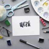 Artysty workspace Słowo praca pisać w kaligrafia stylu, szkła, paintbrush, nożyce, akwarela, paleta na szarym tle Zdjęcia Stock