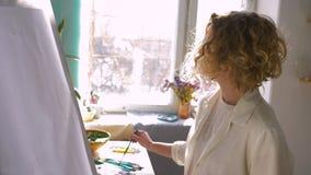 Artysty zawód, Utalentowanego malarza mieszanek żeńskie farby na palecie z grzywny muśnięciem podczas gdy pracujący na nowym obra zdjęcie wideo