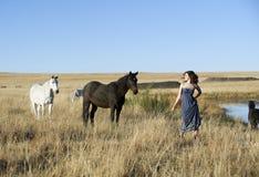 Artystyczna kobieta w polu z koniami Obrazy Royalty Free