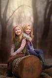 Artystyczny plenerowy portret dwa blond dziewczyny siedzi na beli drzewo w drewna Obraz Stock