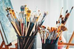 Artystyczny wyposażenie w studiu: obraz, sztaluga, paintbrushes i farby, zdjęcie stock