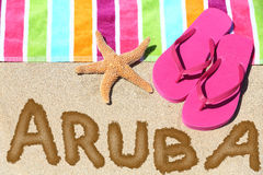 Aruba beach travel. Concept. ARUBA written in sand with water next to beach towel, summer sandals and starfish. Summer and sun vacation holidays stock image