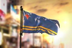 Aruba flagga mot suddig bakgrund för stad på soluppgångpanelljuset Arkivbild