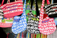Aruba Hand Bags. A display of colourful Aruba hand bags in a store in Orenjedstad, Aruba. In the background are colouful scarves Royalty Free Stock Photography