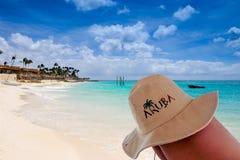 Aruba hat on a leg. Eagle beach on background stock photos
