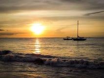 Aruba-Küstensonnenuntergang mit herrlichem Boot im Vordergrund Stockfotografie