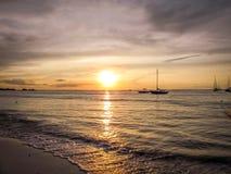 Aruba-Küstensonnenuntergang mit herrlichem Boot im Vordergrund Lizenzfreie Stockfotos