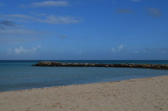 Large Rock Jetty on the Coast of Aruba. Aruba with a large rock jetty jutting into the ocean Stock Images