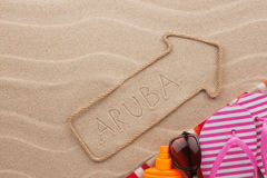 Aruba pointer and beach accessories lying on the sand. As background Royalty Free Stock Photography