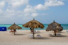 Aruba strand med paraplyer Fotografering för Bildbyråer