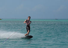 Aruba Wakeboarder with Black Swim Shorts on the Water. Young Aruba wakeboarder with black swim shorts in the water Royalty Free Stock Images